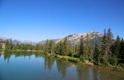 Reflexion im Bogen-Fluss nahe Stadt von Banff in Alberta, Kanada Stockbilder