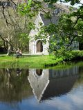 Reflexion: Kyrka för St Finbarrs, Gougane Barra Arkivfoton