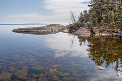 Reflexion in lake of rocky coast. Stock Photography
