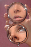 Reflexion in a mirror. Of parts of the face of the beautiful girl Stock Photo