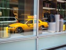 Reflexion på fönstret av en gul taxi i Manhattan Arkivbild