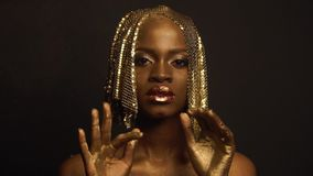 Reflexion. Portrait of glossy african american female model with bright glossy golden makeup posing on black studio. Background. High fashion shooting, Vogue stock video footage