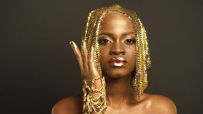 Reflexion. Portrait of Glossy African American Woman with Bright Golden Makeup. Bronze Bodypaint.  stock video