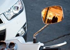 Reflexion in Vespa mirror. Of the man fashion store in Florence Italy  in the mirror white Vespa bike Stock Photo