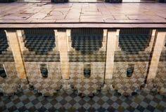 Reflexion von arabischen Bögen in mit Ziegeln gedecktem Pool Stockbild