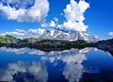 Reflexion von Bergen und von Wolken im alpinen See Stockbilder
