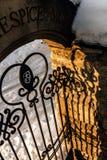Reflexion von einem geschnitzten Gitter auf einem Steinzaun bei Sonnenuntergang Stockfotografie