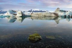 Reflexion von Eiswürfeln mit Moosfelsenvordergrund an der Jokulsarlon-Gletscher-Lagune Lizenzfreies Stockbild