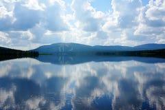 Reflexion von Wolken im See und Hintergrund des Skiweges auf Berg stockfotos