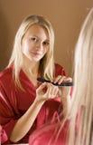Reflexion of young blone woman filing nails. Reflexion of young blone woman in the bathroom's mirror filing nails stock image