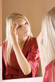 Reflexion of young blone woman removing make-up. Reflexion of young blone woman in the bathroom's mirror removing make-up stock photo