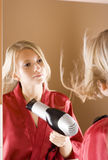 Reflexion of young blone woman using hair drier. Reflexion of young blone woman in the bathroom's mirror using hair drier Royalty Free Stock Images
