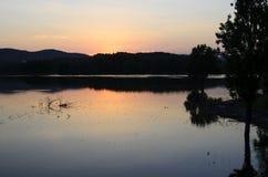 Reflexionen auf dem See bei Sonnenuntergang mit Bäumen Stockfotografie