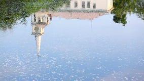 Reflexionen av en kyrklig kyrktorn på flyttningvatten Arkivbild