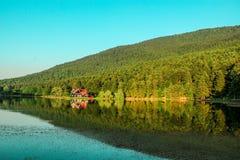 reflexionen av ett hus på vattenyttersida av sjön Royaltyfri Bild