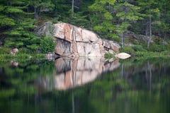 Reflexionen av färgrikt vaggar i sjön Fotografering för Bildbyråer