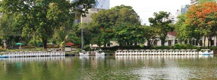 Reflexionen av fartyg i en sjö i ett offentligt parkerar i Bangkok, Thailand Royaltyfri Bild