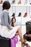 Reflexionen av kvinnan som försöker på höjdpunkt, heeled skor Royaltyfri Fotografi