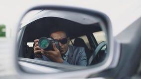 Reflexionen i sidospegel av Paparazzi man sammanträde inom bilen och att fotografera med dslrkameran Arkivbilder