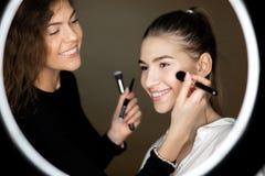 Reflexionen i spegeln av makeupkonstn?ren den charmiga flickan g?r makeup till en h?rlig ung flicka royaltyfri foto