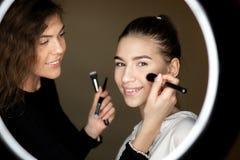 Reflexionen i spegeln av makeupkonstn?ren den charmiga flickan g?r makeup till en h?rlig ung flicka royaltyfria foton