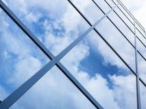 Reflexioner av blå himmel och moln i den glass fasaden av modernt av Royaltyfri Foto
