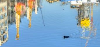 Reflexioner av byggnader och kranar i vatten av skeppsdockan Royaltyfria Bilder