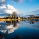 reflexioner av det coutry huset i sjövattnet Arkivfoto