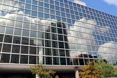 Reflexioner av himmel och moln i stål- och exponeringsglasbuidlings med härlig arkitektur. Arkivfoto