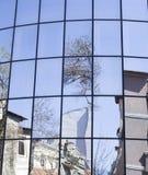 Reflexioner av hus och träd i en ny glass byggnad Royaltyfri Bild