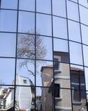 Reflexioner av hus och träd i en ny glass byggnad Arkivbild