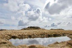 Reflexioner av moln i en bergpöl tarn royaltyfri foto