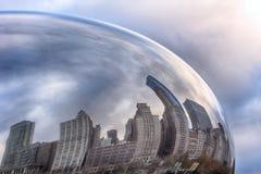 Reflexioner av moln och byggnader på bönan Arkivfoto