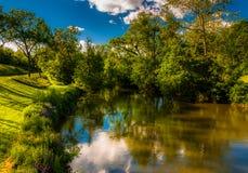 Reflexioner av moln och träd i Antietam Creek, på den Antietam medborgareslagfältet Arkivfoton