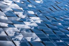 Reflexioner av molnig himmel på en glass fasad Arkivfoto