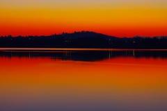 Reflexioner av sjön på Solnedgång-rött royaltyfria bilder