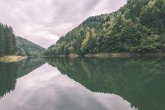 Reflexioner i det lugna sjövattnet - tappningfilmblick Arkivfoton