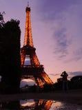 Reflexioner i Paris - Eiffeltorn, en purpurfärgad himmel och en turist Royaltyfria Bilder