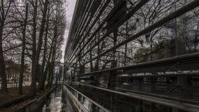 Reflexioner: treeline längs en Munich kanal som avspeglas i en byggnad fotografering för bildbyråer
