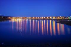 Reflexionerna i en flod från ljusen av en stad i norden av Island som fångas på natten med lång exponering fotografering för bildbyråer