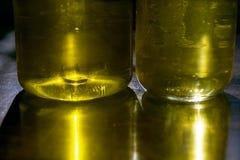 Reflexiones amarillas a través de las botellas de aceite Imagen de archivo libre de regalías