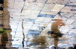 Reflexiones borrosas de la gente en un día lluvioso Foto de archivo