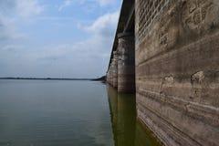 Reflexiones de la fuerza - una pared fuerte de la presa reflejada en agua con el cielo abierto Fotografía de archivo