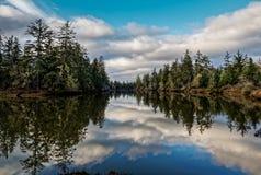 Reflexiones de la nube en el río inmóvil fotografía de archivo