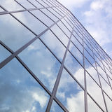 Reflexiones de nubes y del cielo azul en fachada del edificio moderno Foto de archivo libre de regalías