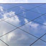 Reflexiones de nubes y del cielo azul en fachada del edificio moderno Fotos de archivo libres de regalías
