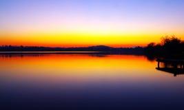 Reflexiones del lago en la puesta del sol con el embarcadero Fotos de archivo