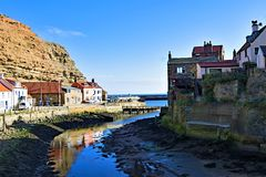 Reflexiones en el puerto de Staithes, cerca de Scarborough, en North Yorkshire foto de archivo libre de regalías