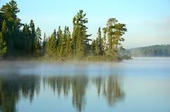 Reflexiones en un lago de niebla wilderness Imágenes de archivo libres de regalías