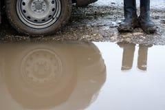 Reflexionshjulbil i en lerig pöl och mäns skor Arkivfoton
